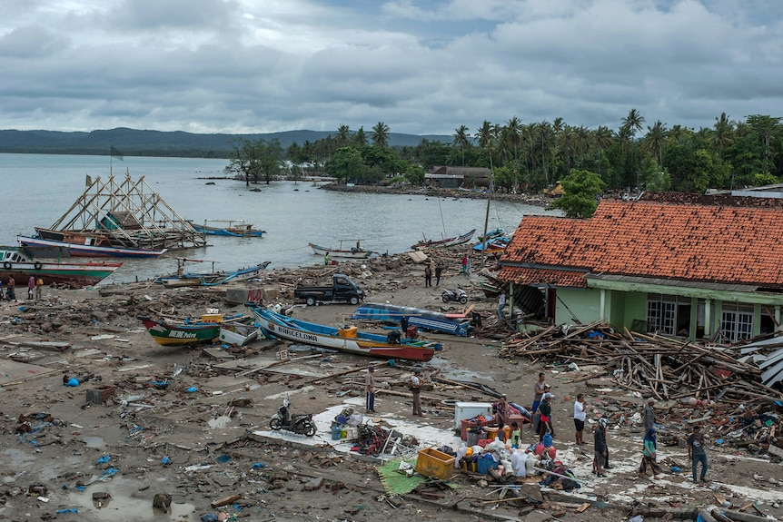 An Indonesian coastal village is pictured from above with streets flattened and debris strewn against a green building.