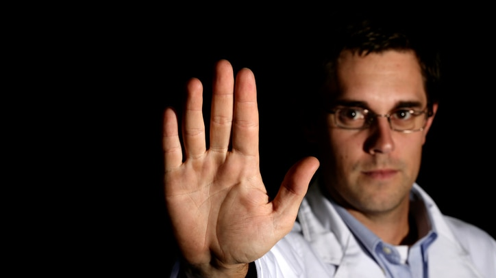 Man in white coat with hand raise in stop signal
