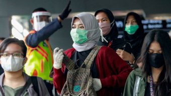 Indonesian women wearing head cover and mask in the crowd.