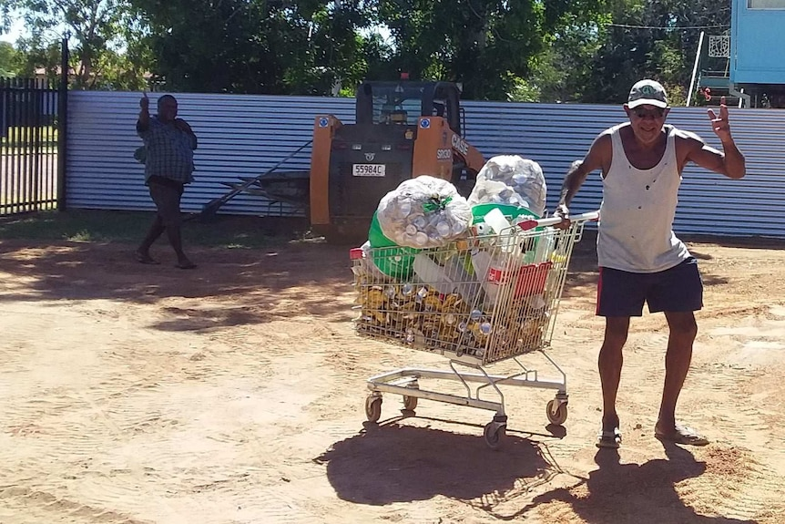 A man waves at the camera, dragging a trolley full of cans.
