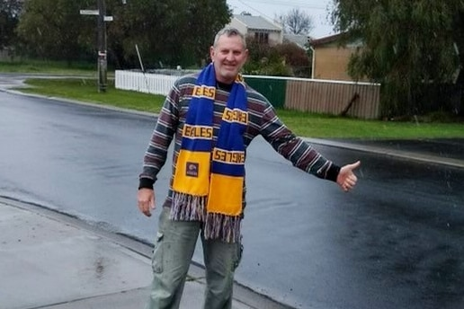 A man standing on a road holding his hand out wearing a west coast eagles scarf