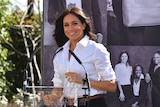 Meghan Markle wearing a white business shirt with butterfly earrings and a stack of bracelets.
