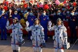 Chinese astronauts Tang Hongbo, Nie Haisheng and Liu Boming wave before the launch of the Long March-2F Y12 rocket.