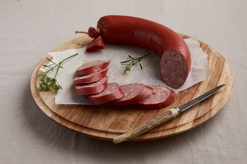 A red sausage on a board partly sliced and partly whole with a knife and parsley