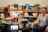 Two women in arms chairs read a children's book in front of a video camera