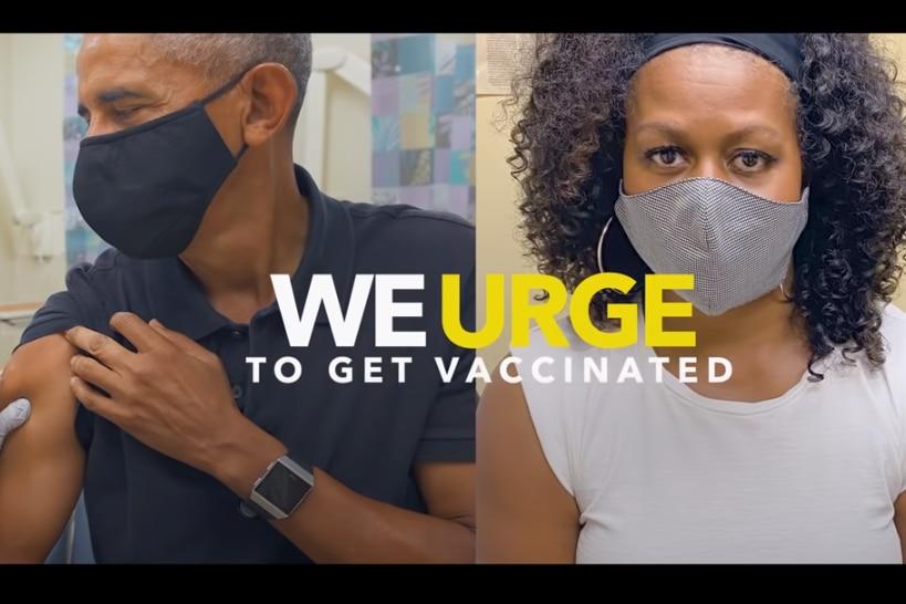 Barack Obama on the left of the screen getting a vaccine, his wife Michelle is on the other side of the screen getting her jab