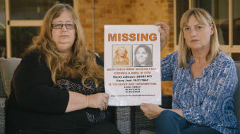 Two women hold up a missing persons poster from the 1970s.