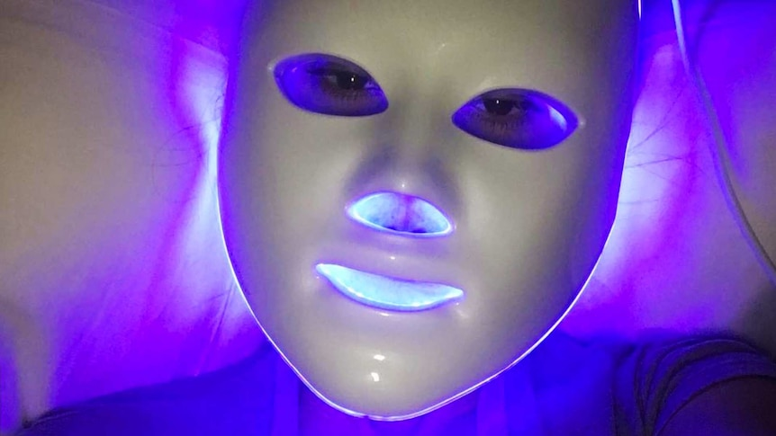Celebrity Kourtney Kardashian using an LED mask for a story about what to know before trying at-home LED masks.