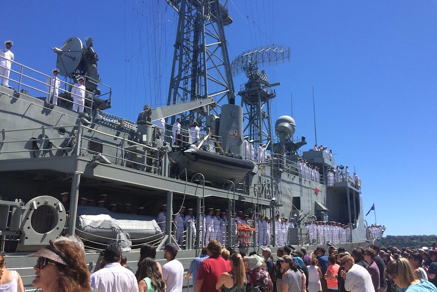 People gather around the departing vessel.