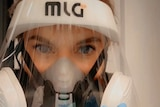 A woman's face with just eyes and eyebrows showing above a mask and perspex face screen as she waves with a blue glove on