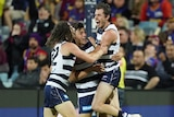Three Geelong AFL players embrace as they celebrate a goal against the Brisbane Lions.