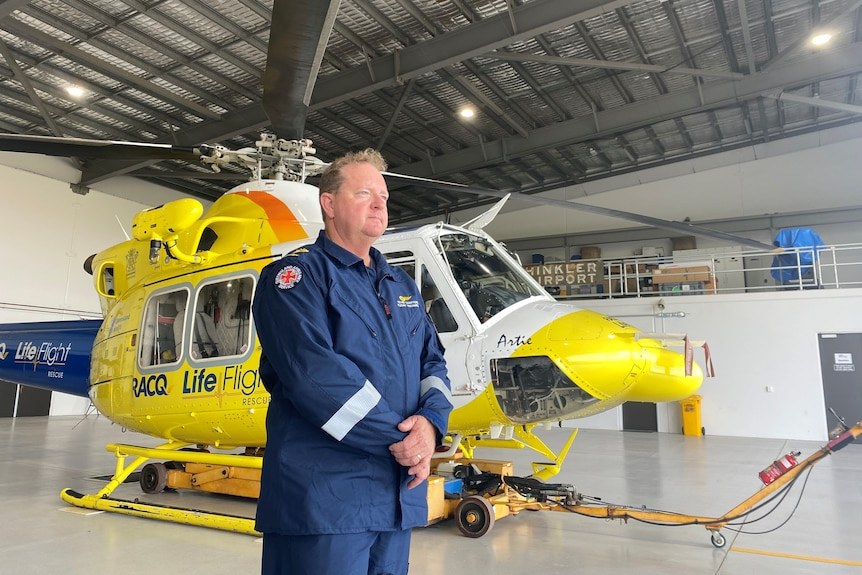 Man in uniform stands beside helicopter