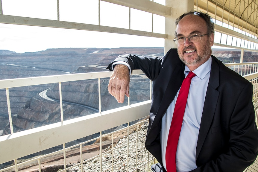 Man in suit standing at a public lookout overlooking a large gold mine
