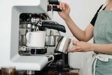 Woman making coffee on an espresso machine