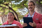 A short smiling Hawaiian woman holding a tray of white towels stands next to a tall smiling white man holding a black folder
