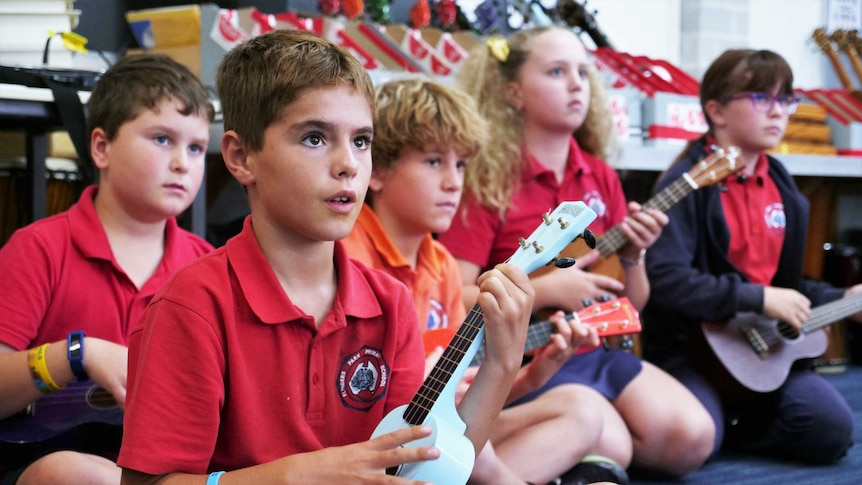 A group of school children sit cross-legged while playing ukuleles.
