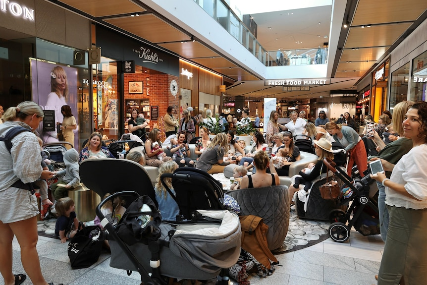A group of people staging a peaceful protest at a shopping centre.