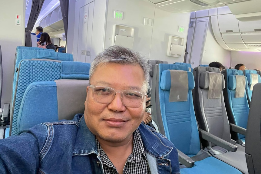 Selfie of a Burmese man with silver hair and glasses sitting on a plane.