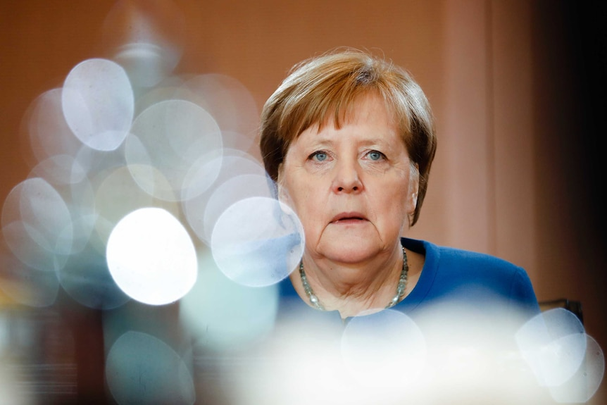 German Chancellor Angela Merkel is seen with a reflection of a pot in the foreground.