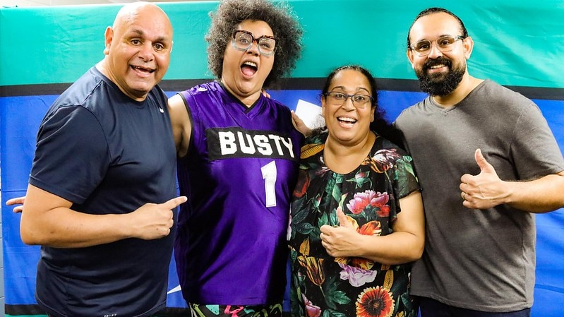 Four comedians pose for picture in front of a Torres Strait flag