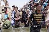A crowd of Afghans stand on a sewage-filled trench at Kabul airport, their faces have been blurred