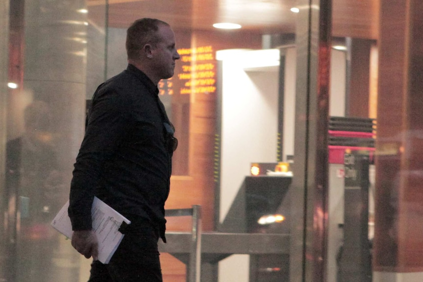 Brett Spits exits the glass doors outside the County Court in Melbourne.