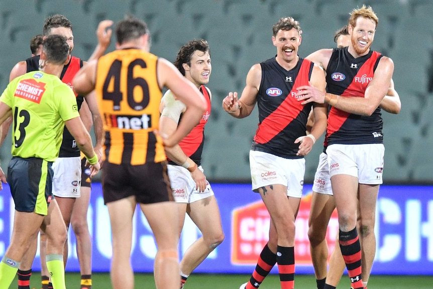 A group of Essendon AFL players celebrate a goal against Hawthorn.