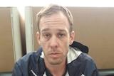 Joshua James Baker sitting down after his arrest