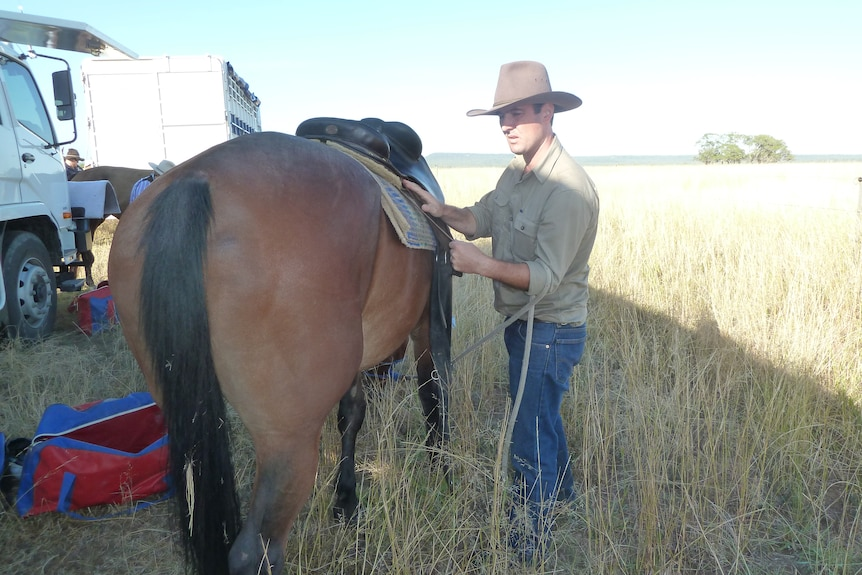 Detective Simon Jackson in a green shirt saddling up a horse in a paddock