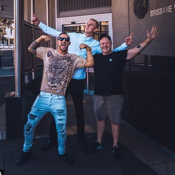 Luke Erwin (rear) with two others in front, with hands up in the air, posing, outside Brisbane watchhouse.