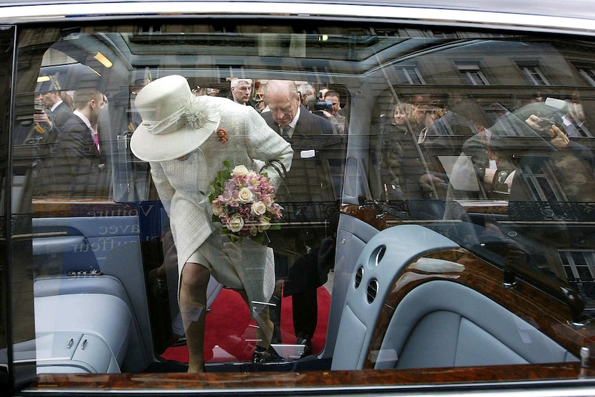 A photo of Queen Elizabeth II and Prince Philip entering a car, taken through the window.