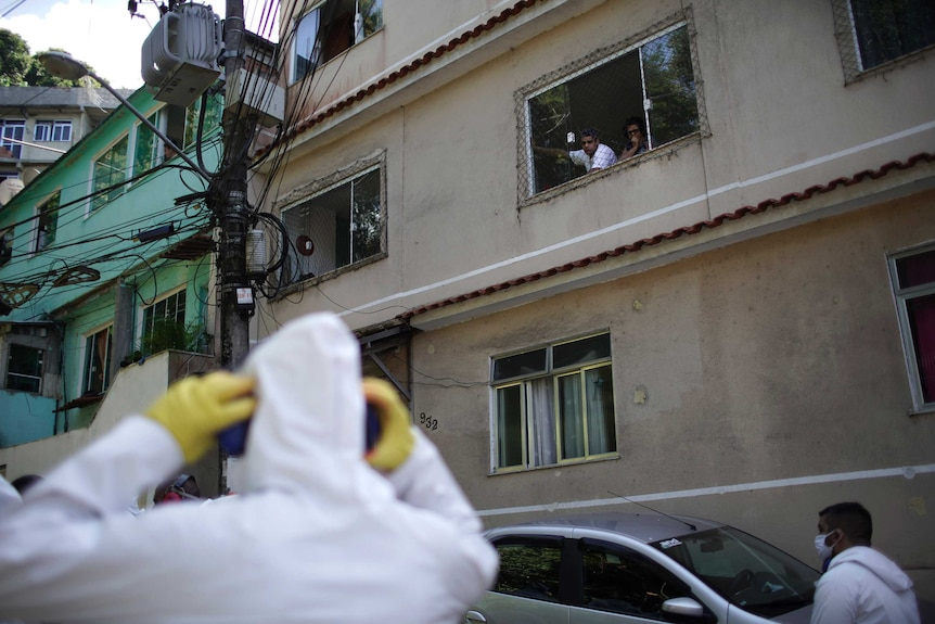 Residents watch water utility workers disinfecting a favela.