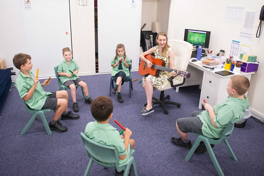 Young students take part in a music lesson with female teacher playing guitar.