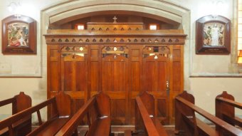 A wooden confessional box sits at the end of a row of pews inside a Catholic church.