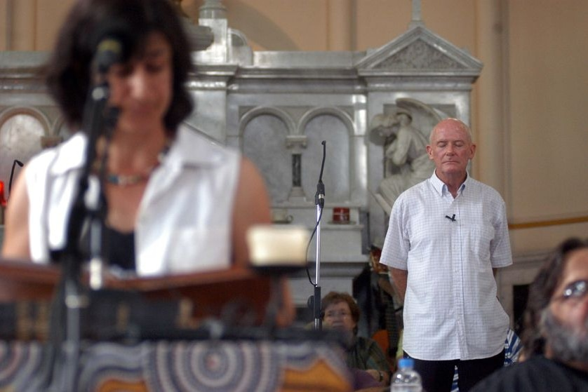A woman delivers a homily in a church while a priest in his 70s stands behind her.