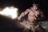 A shirtless man, half squatting, with fire in the nighttime, wearing a headband