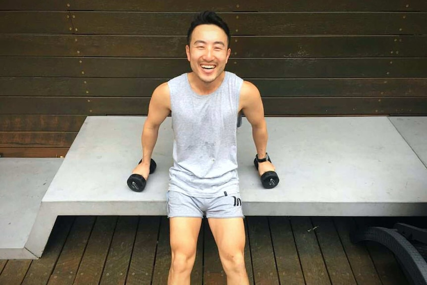 Man does triceps dips using free weights and a bench.