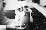 A woman deposits a coin into a piggy bank being held by a man.