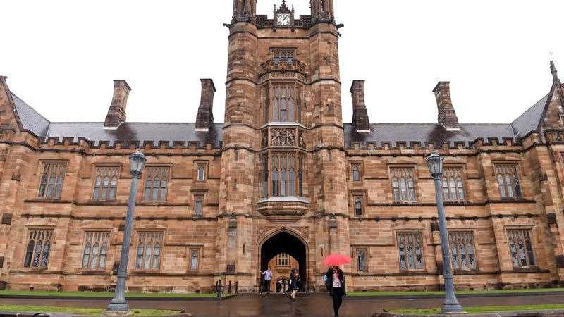 Students walk around the University of Sydney campus on a rainy day.