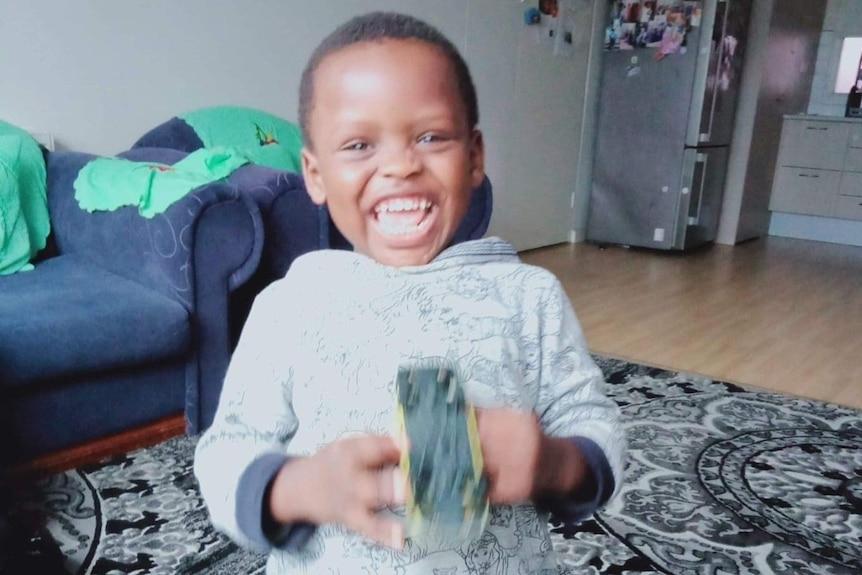 A young boy laughs and looks straight into the camera