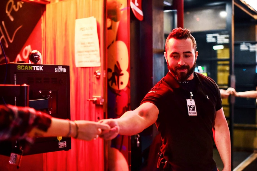 A bouncer standing next to an ID scanner takes ID off patron.