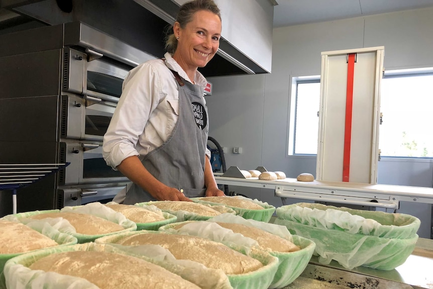 A baker smiling in front of the oven as she puts in the dough she has prepared