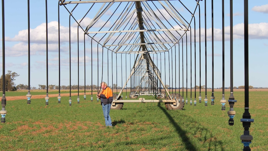 A man in an orange jacket checking nozzles on a lateral irrigator.