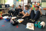 four students in blue uniforms sit on floor with books and pens in front of them engaging in lesson