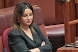 Jacqui Lambie looking down in the Senate.