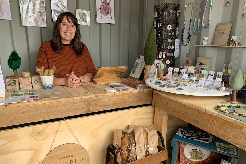 A woman smiles behind a wooden bench displaying jewellery and other items.