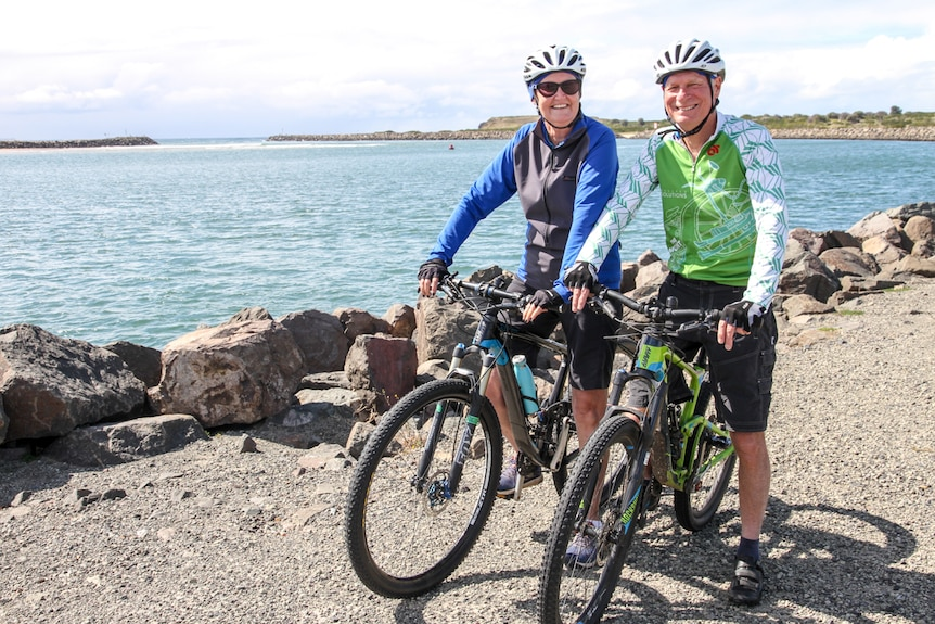 An older couple in cycling gear sit on their bikes in front of a waterway with big smiles on their faces.