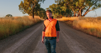 Artist Guido Van Helten wearing high-vis tee standing in middle of unsealed country road.