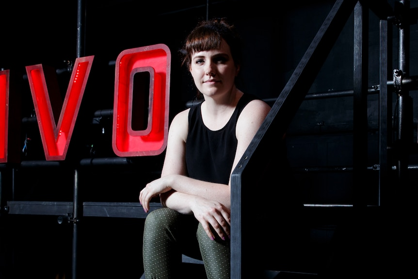 Young woman in black tank top and army-green pants sitting on set with large light-up letters spelling TIVOLI behind her in red.