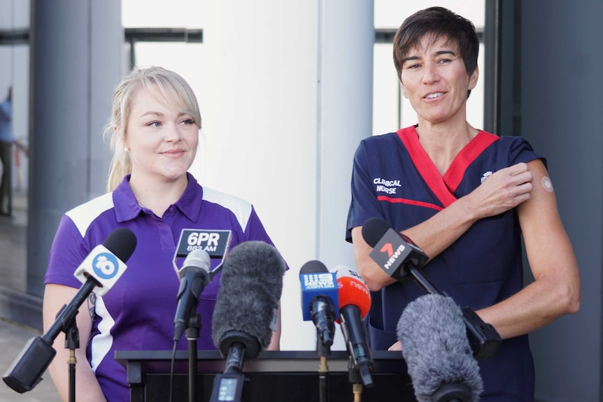 Two nurses standing at a podium speaking to journalists, smiling, with one woman showing a bandaid on her arm from the vaccine.